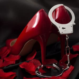 BDSM, prostitution and deviant sexual behaviour concept with handcuff restraints, a riding crop, red high heeled stilettos, rose petals and with the crop running under the high heels of the shoes on black silk