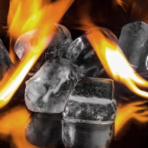 Image of ice cubes and orange flames against a dark background to illustrate a blog on Temperature play